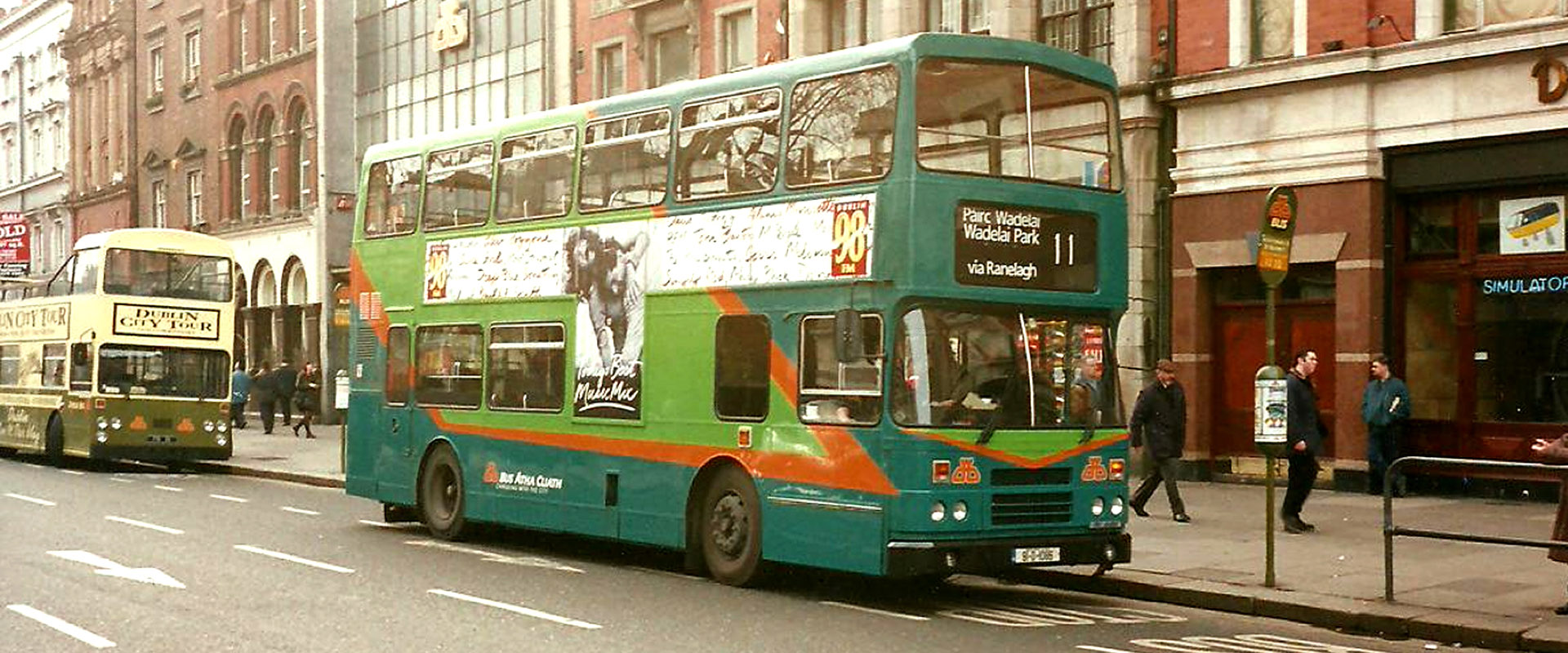 Dublin Bus on O'Connell Street with a two-tone green livery with orange.