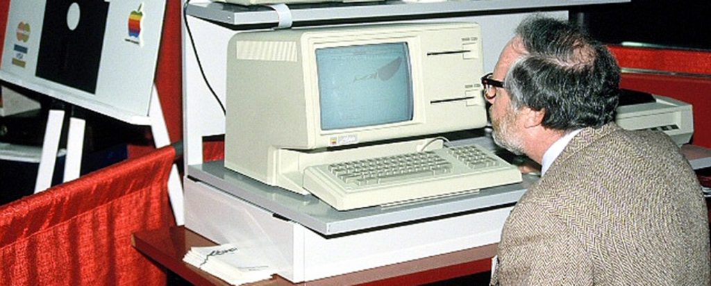 A picture of a man using a computer in the 1980's.