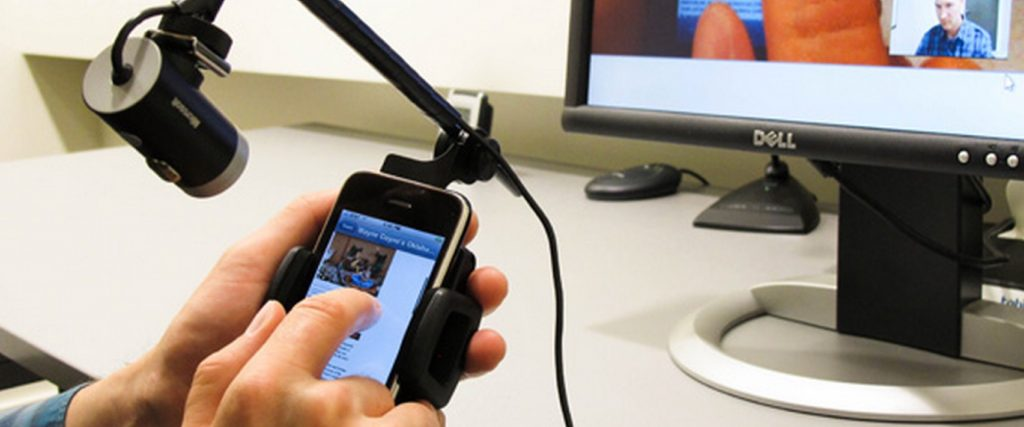 A photograph of a usability test. The user is using an iphone while a camera attached records their movements. There is also a desktop in the background showing the users face and live video.