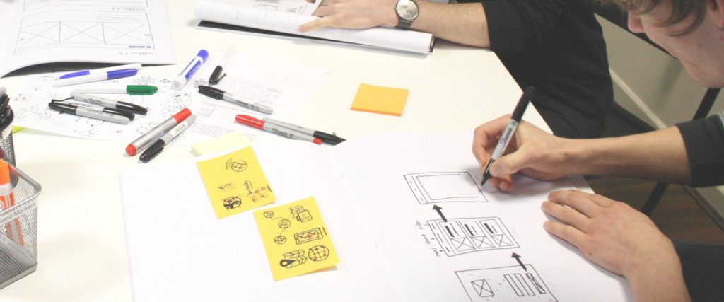 A picture of a person designing a paper prototype