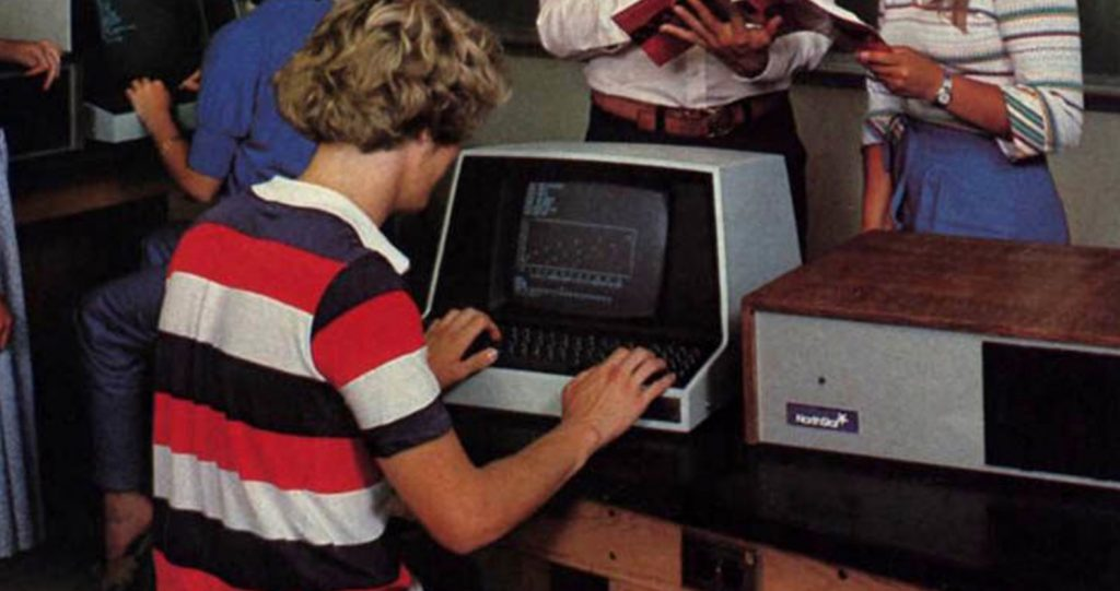 A photograph of a man using a computer in the 1980's.