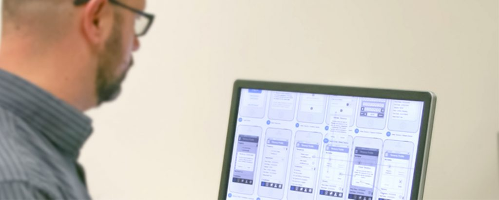 A person look at a mobile interface prototype on a desktop.