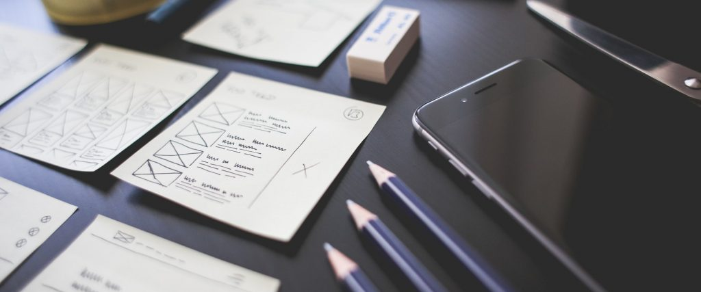 A table with sketches of UI and a mobile phone